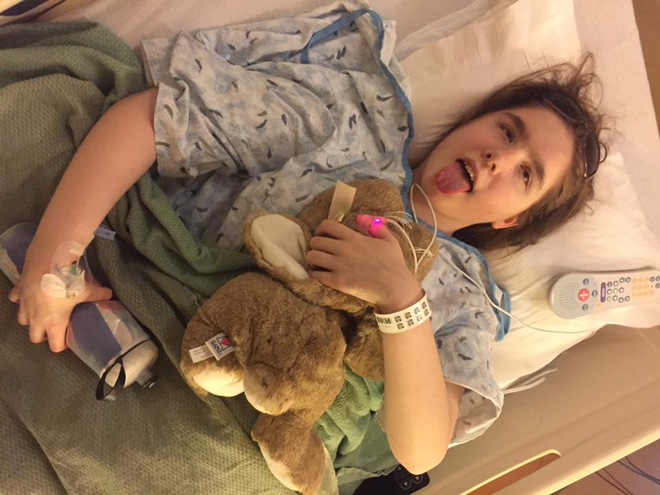 Rachel sitting in a hospital bed sticking our her tongue playfully