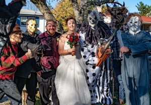 Kat wasabi in wedding gown surrounded by husband, todd woodward and scary guys in halloween costumes
