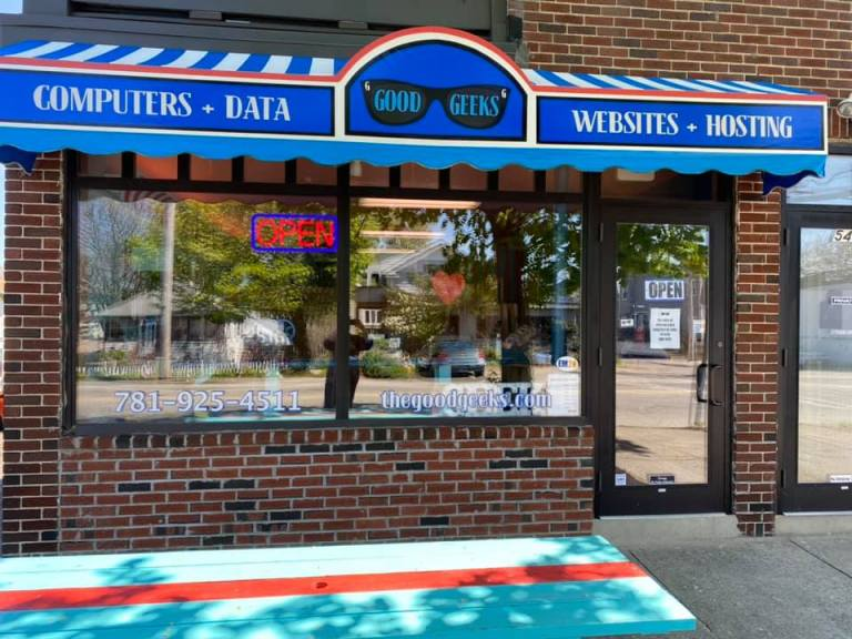 Outside photo of good geeks shop located in a brick buolding with a blue awning that says good geeks